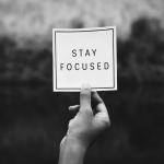 "hand holding up a sign that says, ""stay focused"""